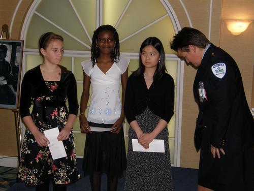 Patricia-Ann Bourgeois, agente communautaire au service de police du poste de quartier 11, Notre-Dame-De-Grâce, organisatrice du concours « Un monde sans racisme » , accompagnée des trois élèves primés.