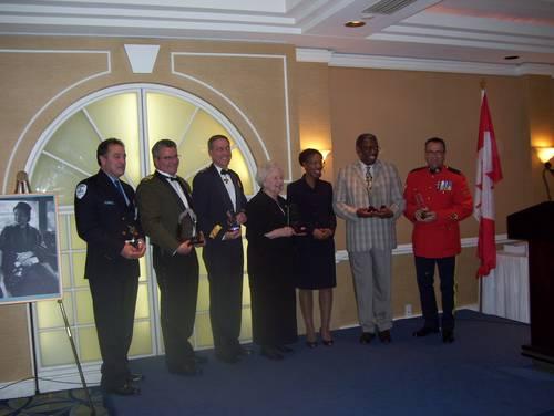 De gauche à droite, Michel Lapierre (SPVM), agent au module Soutien Technique; Inspecteur Tremblay (SQ), représentant le District de la Mauricie-Centre-du-Québec; Lieutenant-général M.J. Dumais, Commandant de Commandement Canada et Champion de la Défense nationale pour les minorités visibles; Sœur Andrée Ménard, fondatrice de l'organisme PROMIS; Yolande James, ministre de l'Immigration et des Communautés culturelles; Keder Hyppolite, directeur général de SANQI; Caporal Sylvain L'Heureux (GRC, Division C)