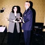 Madame Patricia Rimok, présidente du Conseil des Relations interculturelles, remet le trophée à M. Yves Charrette