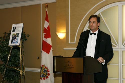 Allocution de M. Lee McClenny, Consul général des Etats-Unis. À gauche de l'écran, portrait de Virginia Durr