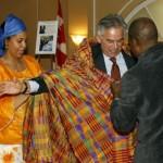 M. Ghislain Picard, Chef régional de l'Assemblée des Premières Nations, Québec/Labrador, revêt la tenue traditionnelle, aidé par M. Georges Konan et Johanne